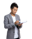 Asian businessman write on clipboard Royalty Free Stock Photo