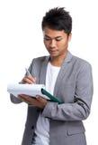 Asian businessman write on clipboard Royalty Free Stock Photos