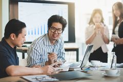 Business workers group meeting in office. Asian businesspeople discussing and brainstorm with young freelance men in meeting room. Business company co-operate Royalty Free Stock Image