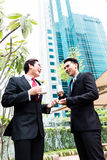 Asian businesspeople drinking coffee outside Royalty Free Stock Image