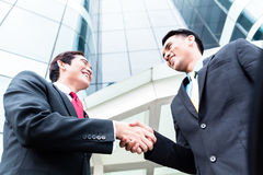 Asian businesspeople handshake in front of high rise building Stock Photography