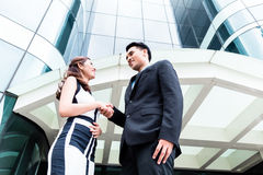 Asian businesspeople handshake in front of high rise building Royalty Free Stock Image