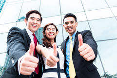 Asian businesspeople outside in front of skyscraper Royalty Free Stock Photography