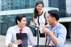 Asian businesspeople working outside with coffee Stock Photos