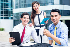 Asian businesspeople working outside with coffee Royalty Free Stock Images