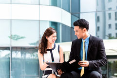 Asian businesspeople working outside on documents Royalty Free Stock Photography