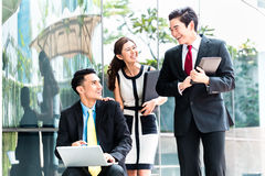 Asian businesspeople working outside on laptop Stock Images