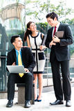 Asian businesspeople working outside on laptop Stock Image