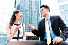 Asian businesspeople working outside on laptop Royalty Free Stock Photos