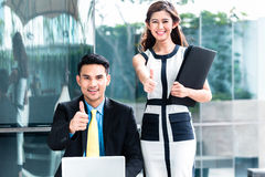 Asian businesspeople working outside on laptop Royalty Free Stock Photography