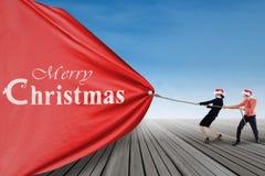 Asian businessteam pull christmas banner Royalty Free Stock Image