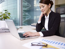 Asian businesswoman. Looking at laptop computer in office Stock Photography