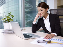 Asian businesswoman. Looking at laptop computer in office Royalty Free Stock Photo