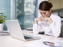 Asian businesswoman. Sitting and thinking in office, looking tired royalty free stock photo