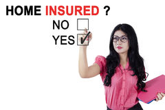 Asian businesswoman approving business insured. Image of Asian businesswoman is approving business insured while holding document and a pen in the studio Royalty Free Stock Photo