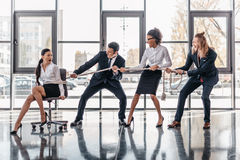 Asian businesswoman bound with rope on chair and multicultural business team pulling her Stock Photo