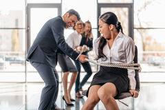 Asian businesswoman bound with rope on chair and multicultural business team pulling her Royalty Free Stock Photos