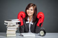 Asian businesswoman with boxing glove ,books and clock Royalty Free Stock Image