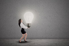 Asian businesswoman carry light bulb. Asian businesswoman is carrying bright light bulb on grey background Stock Photography