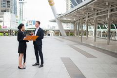 Asian businesswoman and caucasian businessman holding document file on hand and talk about business future. In the city stock images