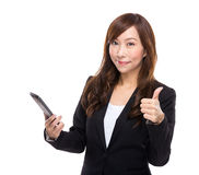 Asian businesswoman with cell phone and thumb up Royalty Free Stock Photography