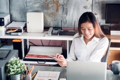 Asian businesswoman chattin on mobile phone in front of laptop c Royalty Free Stock Photography