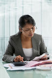 Asian businesswoman checking bills Stock Images