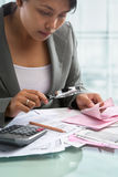 Asian businesswoman checking bills Royalty Free Stock Photography