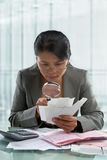 Asian businesswoman checking bills Stock Photo