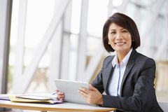 Asian businesswoman with digital tablet, smiling to camera royalty free stock images