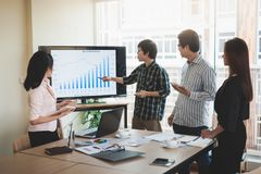 Business workers group meeting in office. Asian businesswoman discussing and brainstorm with young freelance men in meeting room. Business company co-operate Royalty Free Stock Photo