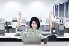 Asian businesswoman with dollars on laptop Royalty Free Stock Photography