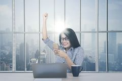 Asian businesswoman expressing her success. Portrait of Asian businesswoman reading good news on the smartphone with expressing her success near the window Stock Photography