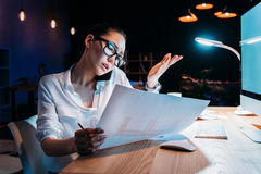 Asian businesswoman in eyeglasses holding blueprint and talking on smartphone Stock Image