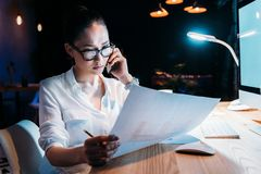 Asian businesswoman in eyeglasses holding blueprint and talking on smartphone Royalty Free Stock Photo