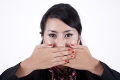 Asian businesswoman with fingers on lips. Attractive businesswoman with fingers on lips isolated on white Royalty Free Stock Photos