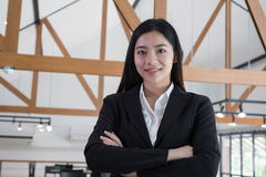 Asian businesswoman with folded hands smiling at camera. confide Royalty Free Stock Photos