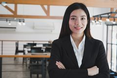 Asian businesswoman with folded hands smiling at camera. confide Royalty Free Stock Photography