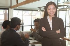 Asian businesswoman with folded hands smiling at camera. confide Royalty Free Stock Photo