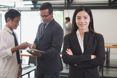 Asian businesswoman with folded hands smiling at camera. confide Royalty Free Stock Image