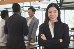 Asian businesswoman with folded hands smiling at camera. confide Stock Photography