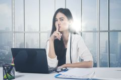 Asian businesswoman gesturing silence sign. With her forefinger over lips while working with a laptop near the window Stock Images