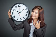 Asian businesswoman hold a clock thumbs up and smile Royalty Free Stock Photography