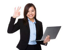 Asian businesswoman hold with laptop computer and ok sign gestur Stock Image