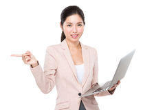Asian Businesswoman holding a laptop computer and pen point asid Royalty Free Stock Photography