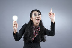 Asian businesswoman with Idea. Beautiful asian businesswoman holding a light bulb while smiling Royalty Free Stock Photo