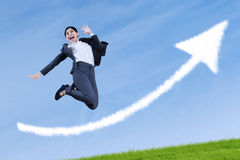 Asian businesswoman jumping of winning. With arrow up sign Royalty Free Stock Photo