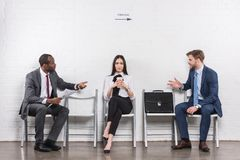 Asian businesswoman listening to multicultural businessmen having conversation while waiting. For job interview stock photos