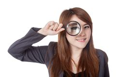 Asian businesswoman look through magnifying glass and smile Royalty Free Stock Image