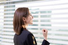 Successful asian business woman. Asian businesswoman look window out and cheer for herself in the office stock image